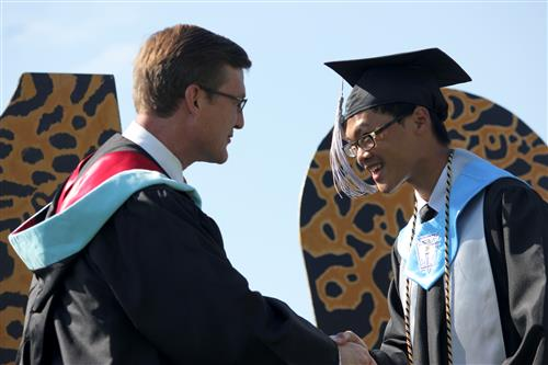 Superintendent W. Jeffrey Booker shakes the hand of a graduate at Forestview High School