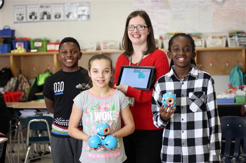 Pleasant Ridge Elementary Teacher Rebecca Cissell poses for a picture with her fourth grade students.