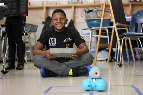 A Pleasant Ridge Elementary student programs a robot to perform a task.
