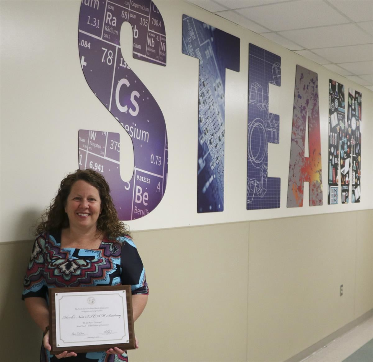 Dr. Jill Payne, principal of Hawks Nest STEAM Academy, shows off the North Carolina STEM School of Distinction award.